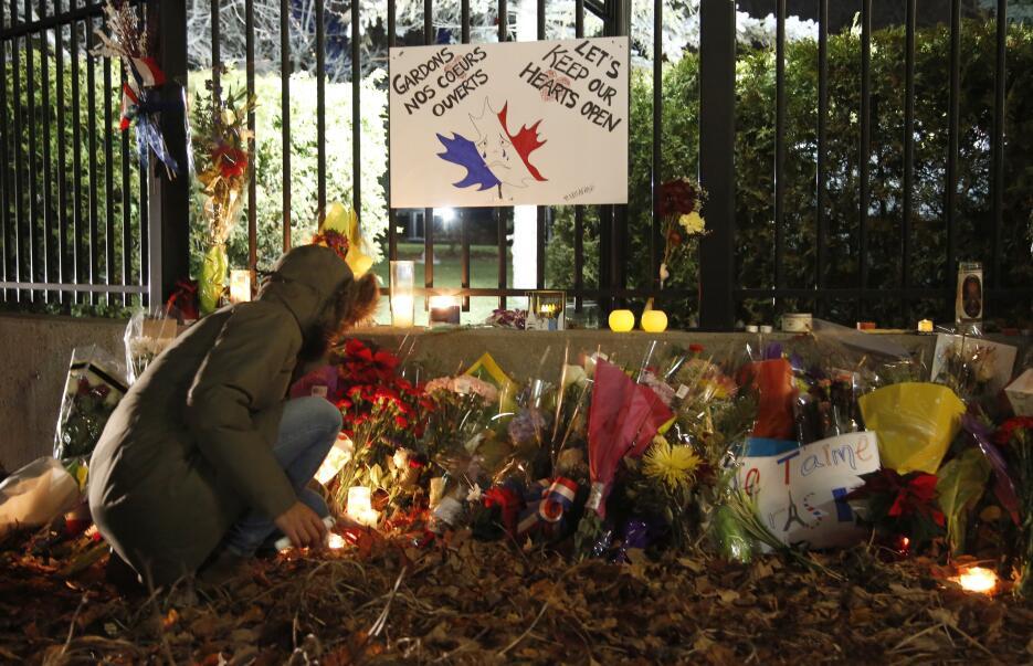 Una mujer enciende una vela frente a la embajada de Francia en Ottawa