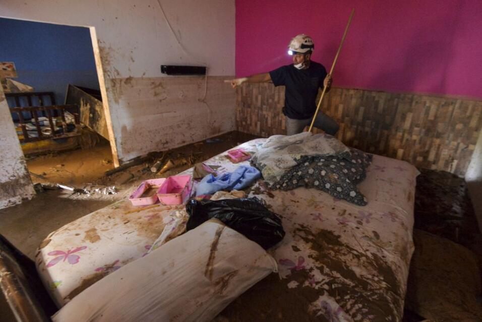 Un bombero busca sobrevivientes dentro de una casa inundada por el lodo...