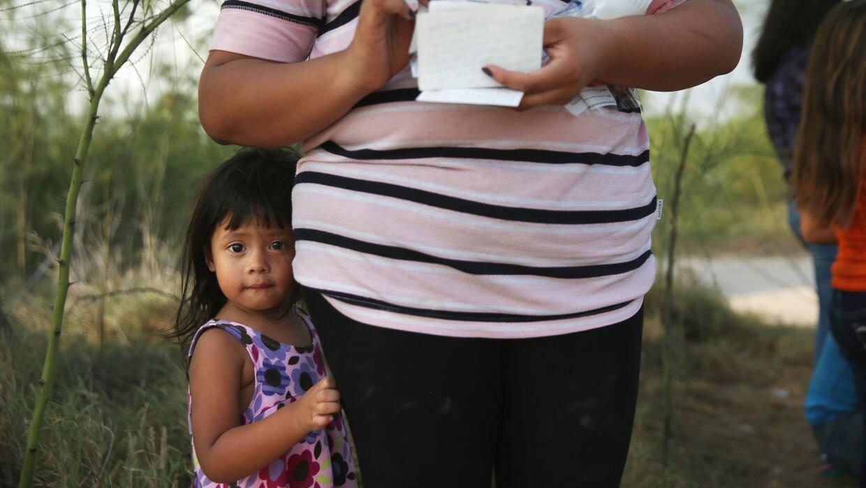 Una niña migrante indocumentada junto a su madre en un punto de la front...