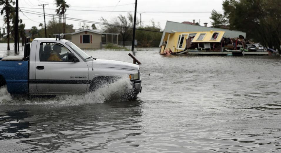 Un camión transita una calle inundada frente a una casa destruida...