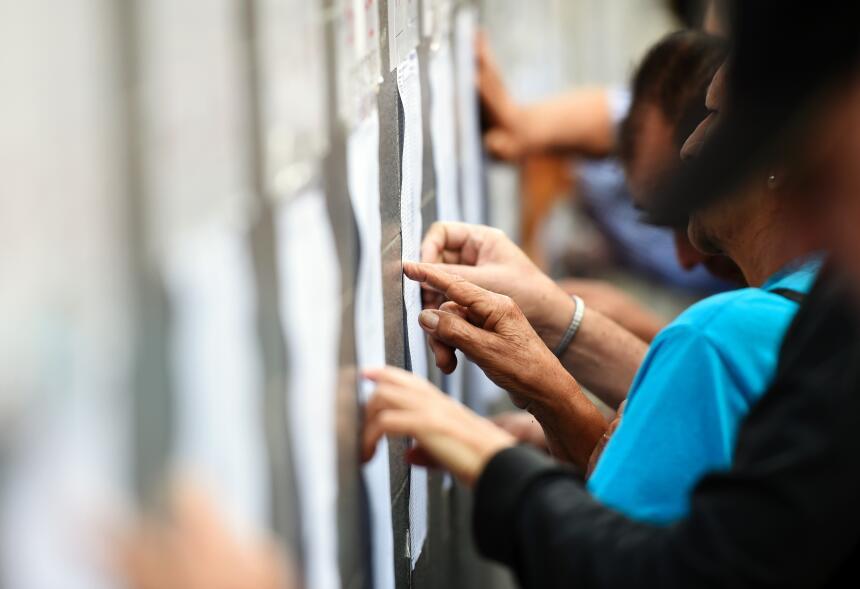 Votantes buscando su nombre en las listas de un centro de votación en Ca...