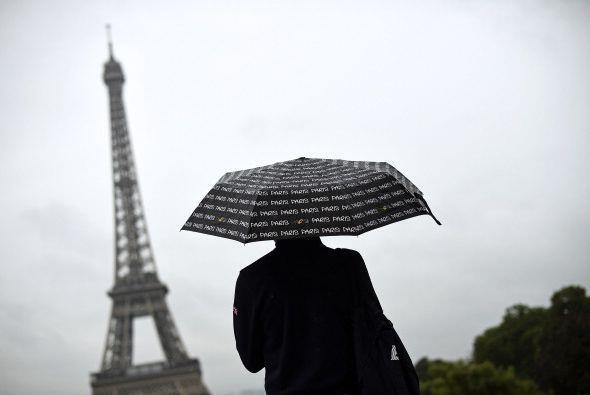 Un turista mira hacia la Torre Eiffel cubriéndose con un paraguas de la...