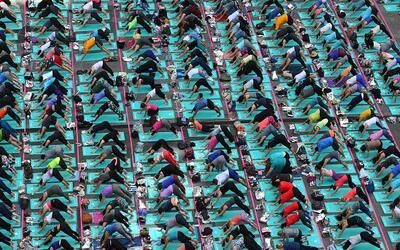Una multitud de personas participa en una sesión masiva de yoga e...
