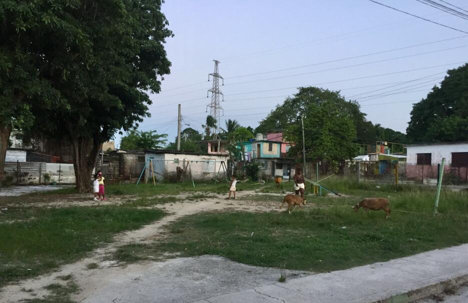In Vieja Linda children play on rusty, broken swings in a park, as other...