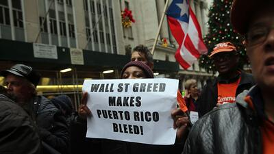 People protest outside of Wall Street against cutbacks and austerity mea...
