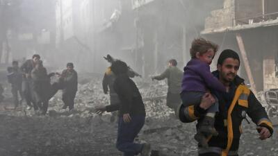 Un hombre sirio rescata a un niño herido en un bombardeo del gobierno si...
