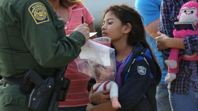 Durante la crisis migratoria de 2014, una niña salvadoreña observa a un...