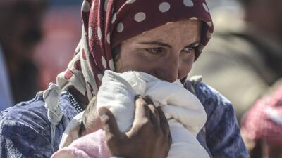 Una refugiada siria abraza a su hijo en una playa del Mediterráneo. Más...