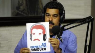 Con los auriculares puestos y micrófonos de radio, Maduro señaló que se...