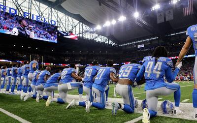 Jugadores de los Detroit Lions, propiedad de la familia Ford, se arrodil...