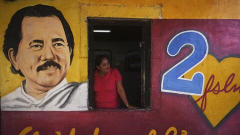 Una mujer en una casa pintada con el rostro del presidente Daniel Ortega...