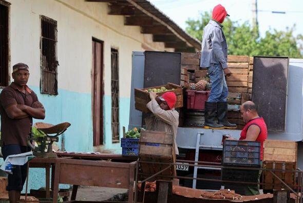Varios hombres descargan vegetales de un camión en un mercado de...