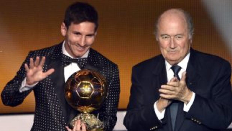El jugador argentino es flanqueado por el máximo dirigente de la FIFA du...