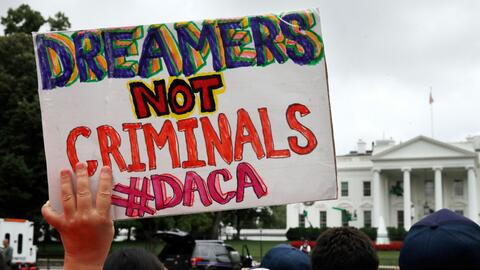 A woman holds up a sign in support of DACA in front of the White House,...