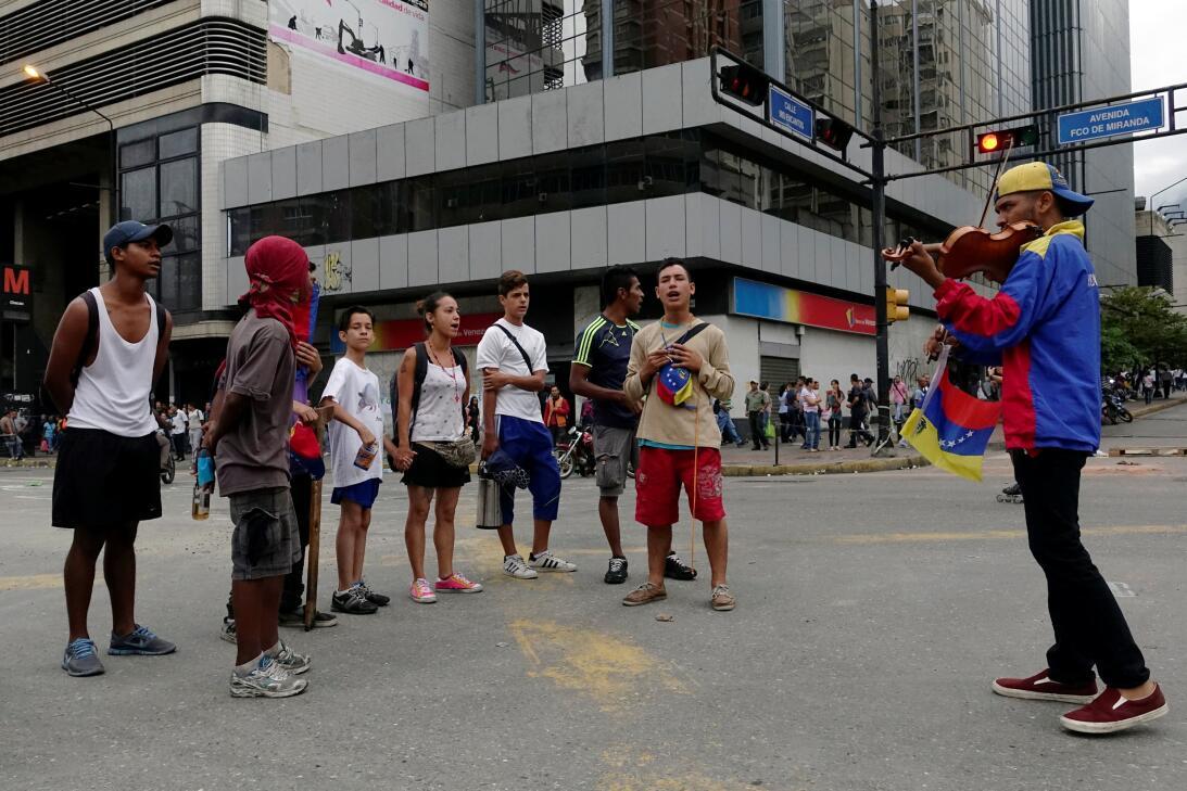 Un grupo de jóvenes manifestantes cantan el himno nacional de Venezuela...