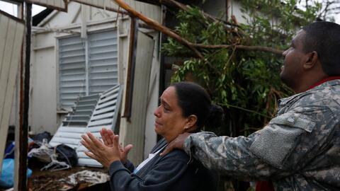 Una familia frente a su casa devastada en el pueblo de Guayama, Puerto R...