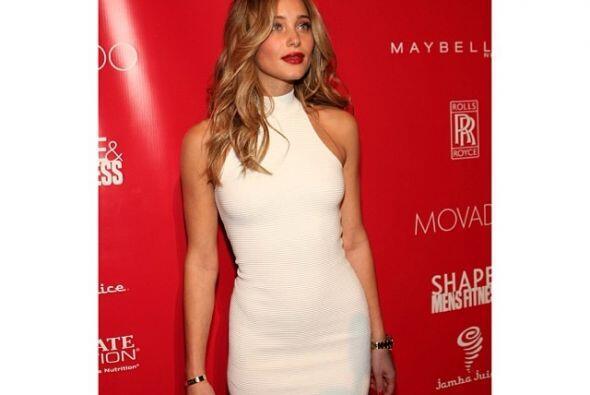 Hannah en una alfombra roja, con un ceñido vestido blanco.