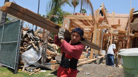 Trabajador transporta unas tablas en las obras de una casa en Beverly Hills