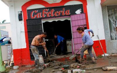 Empleados limpian un negocio que resultó dañado cuando el...