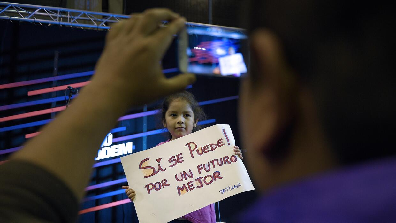 Una niña con un cartel en un acto electoral.