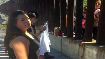 Familia se reencuentra a través del muro fronterizo