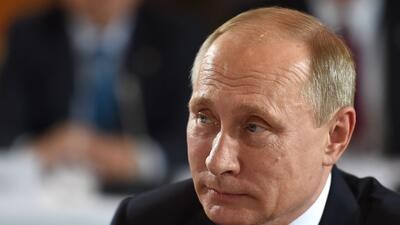 Russian President Vladimir Putin poses ahead of a meeting at the chancel...