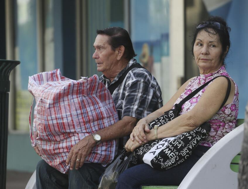 Cira Delia Rodriguez and her husband Jesus Mundia, wait for a bus to tak...