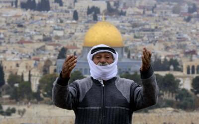Un hombre reza delante de la mezquita de Al Aqsa en Jerusalén, ci...
