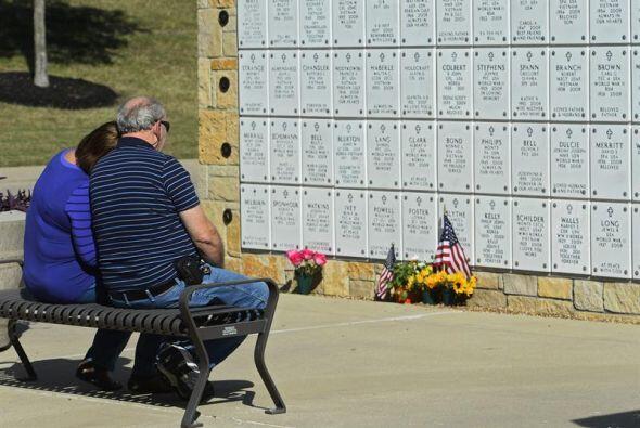 Una pareja se sienta en una banca frente a los osarios de cientos de sol...
