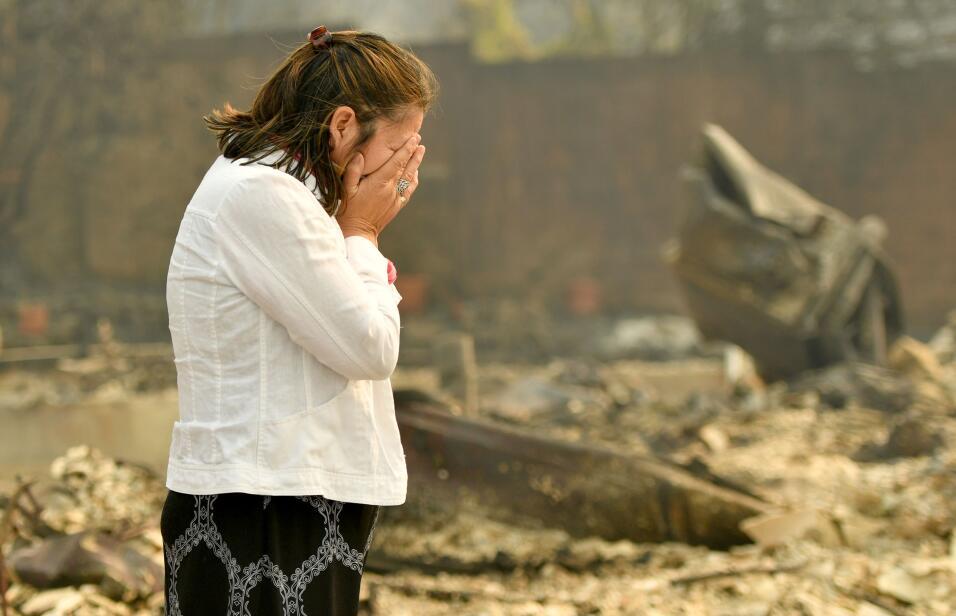 Martha Márquez llora frente a su casa incendiada en Santa Rosa, C...