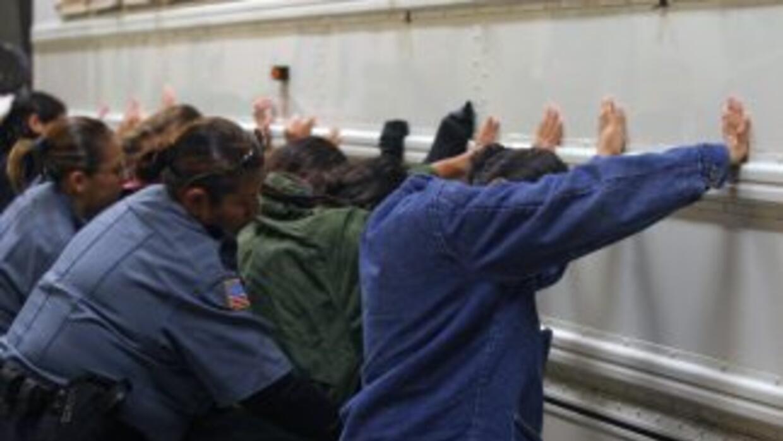 Inmigrantes detenidos son revisados por agentes federales de inmigración...