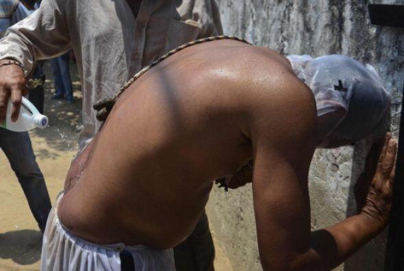 Un hombre vierte alcohol en el coxis de un devoto en Santo Tomás, depart...