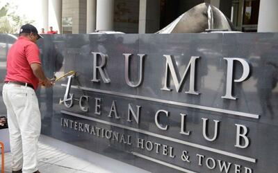 A worker removes the Trump name from a hotel in Panama that was managed...