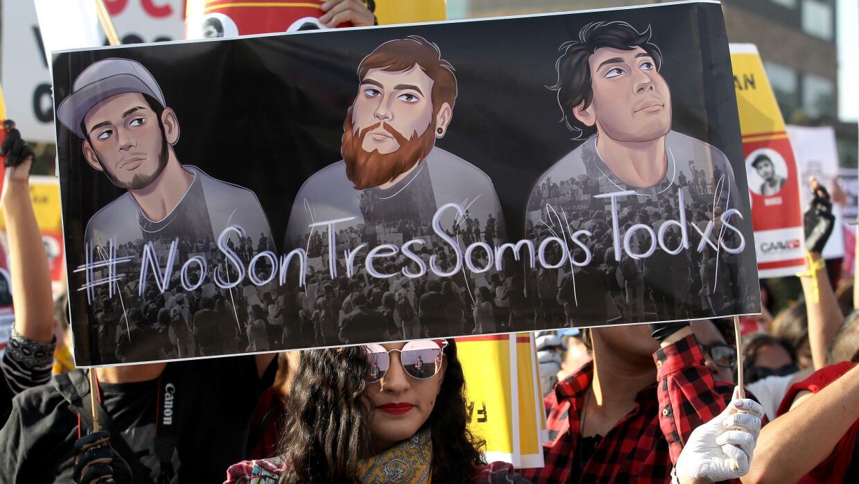 Una joven con un cartel de los tres estudiantes de la Universidad de Med...