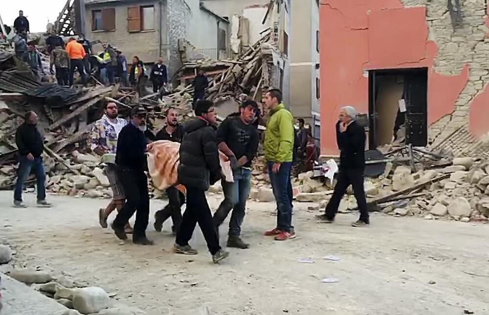 Voluntarios y bomberos recogen un cadáver en Amatrice