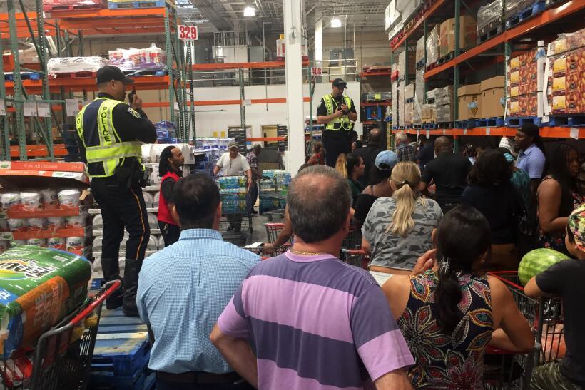 Agentes de la policía controlan las compras en una tienda Costco de Miami.