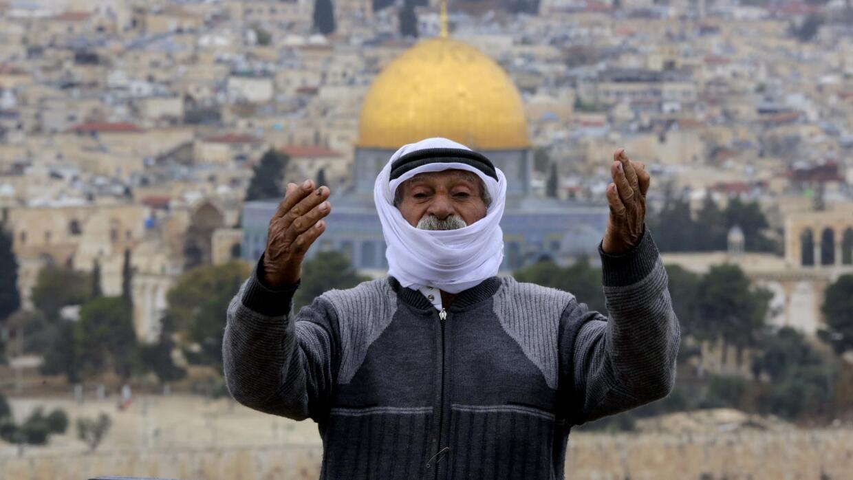 Un hombre reza delante de la mezquita de Al Aqsa en Jerusalén, ciudad co...