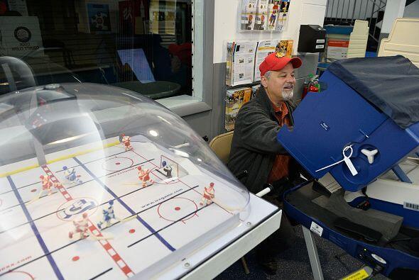 Jim Norman sufraga en una máquina de votación electrónica instalada en u...