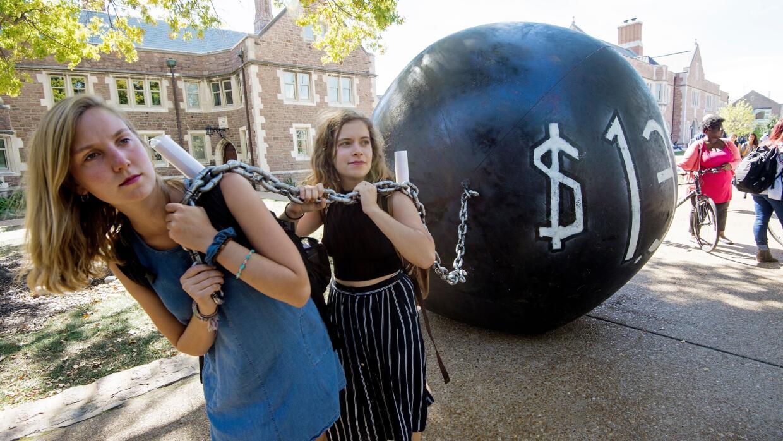 Estudiantes arrastran una bola con un grillete que simboliza la deuda qu...