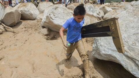 Un niño camina entre el lodo recogiendo escombros en la zona de Mocoa, a...
