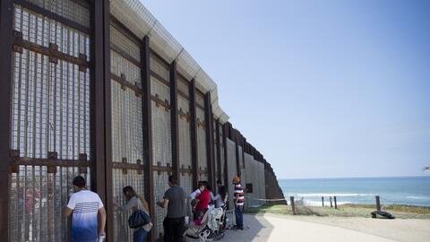 Familias de inmigrantes conversan a través de la barda que divide...