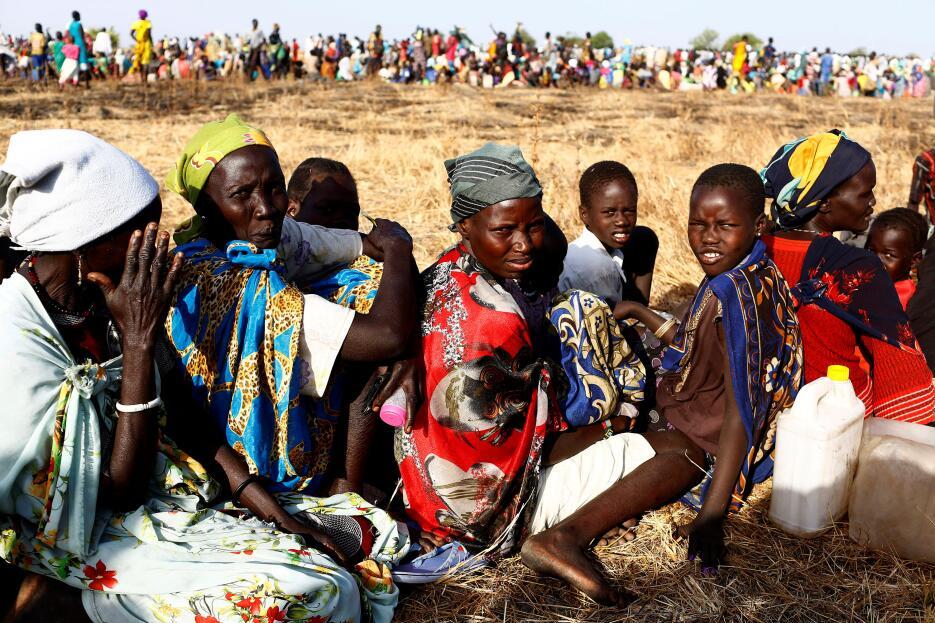 Sudán del Sur: Mujeres y niños hacen cola para conseguir comida en un pu...