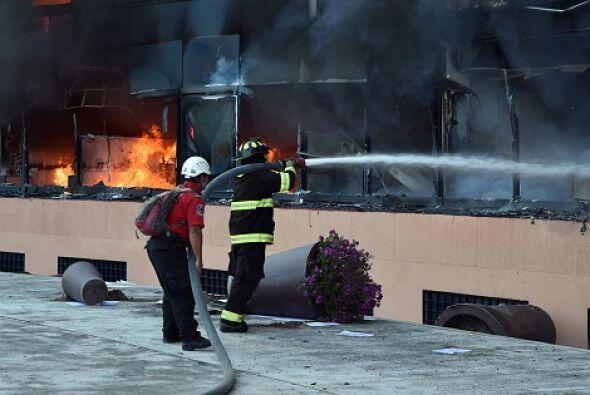 Algunos bomberos trataban de apagar el fuego.