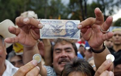 Un hombre muestra un billete de veinte pesos en las calles de la Ciudad...