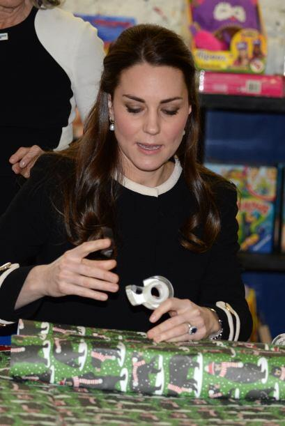 Con gran habilidad, Kate ponía cinta sobre el papel y sostenía la caja.