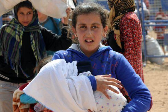 Una niña siria ayuda a su madre a cargar a un bebé, mientras cruzan la v...