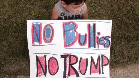 """Un niño de 6 años sostiene una pancarta que traduce """"..."""