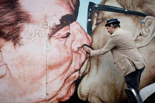 El artista ruso Dimitri Vrubel limpia su pintura que representa el líder...