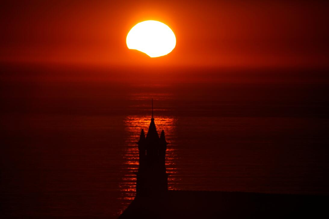 The Saint-They Chapel is seen in silhouette at sunset during a partial s...
