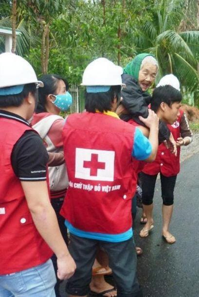 Personal de la Cruz Roja ayuda a evacuar a una anciana en Danang, Vietna...
